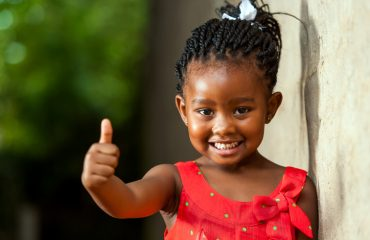 Pretty little african girl showing thumbs up.